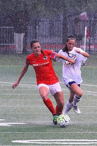 Houston's Cami Privett (left) attempts to move the ball downfield against pressure from both FC Dallas' Gwennie Puente (right) and a torrential downpour that occurred during the game. (Photo: David Wilfong)